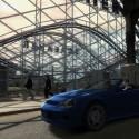 A blue sports car drives past a fairground. | Views: 1883