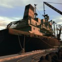 A large ship moored at the docks with some builders nearby. | Views: 1238